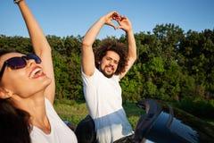 Krullende donker-haired jonge man die zijn handen omhoog houden die, met een mooie jonge vrouw in zwarte cabriolet op zonnig zitt stock foto's