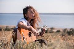 Krullende donkerbruine meisje het spelen gitaar en het zingen op het gebied op de helling van Golf stock foto