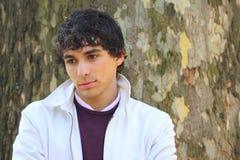 Krullende haired jonge volwassen mens in wit, met een boom Stock Foto