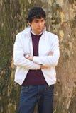 Krullende haired jonge volwassen mens in wit, met een boom Royalty-vrije Stock Fotografie