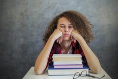 Krullende het meisjesrust van de haartiener van het leren op boeken Royalty-vrije Stock Foto's