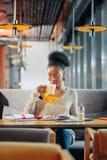 Krullende internationale student die yummy latte in cafetaria drinken stock fotografie