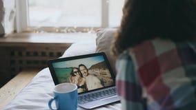 Krullende jonge vrouw die online videopraatje met vrienden hebben die laptop camera met behulp van terwijl het liggen op bed Royalty-vrije Stock Afbeelding