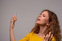 Krullende jonge vrouw in gele kleren ongelukkig met haar verschijning Stock Foto