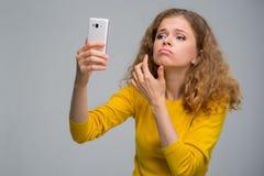 Krullende jonge vrouw in gele kleren ongelukkig met haar verschijning Royalty-vrije Stock Foto's