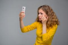Krullende jonge vrouw in gele kleren ongelukkig met haar verschijning Royalty-vrije Stock Foto