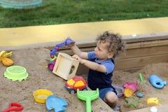 Krullende jongen bij zanddoos Royalty-vrije Stock Afbeelding