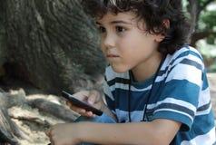 Krullende jongen met cellphone Stock Foto