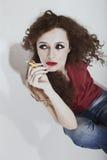 Krullende langharige donkerbruine vrouw met gele sigaret Stock Foto's