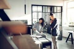 Krullende medewerker die van binnenlandse ontwerper hem over het project vertellen stock fotografie