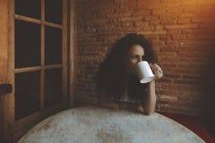 Krullende meisje het drinken thee of koffie in koffie Royalty-vrije Stock Foto's