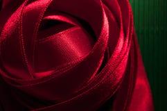 Krullende ontwerp van het close-up het Rode Lint op groene textuur Royalty-vrije Stock Fotografie