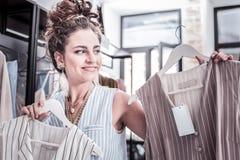Krullende ontwerper met haarbroodje die het doordringen in haar neus hebben die nieuwe kleding voorstellen stock foto