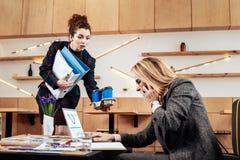 Krullende secretaresse die meeneemkoffie brengen aan vrouwelijke werkgever royalty-vrije stock fotografie