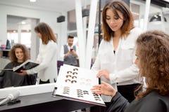 Krullende vrouwelijke cliënt die een kleur voor hait het stemmen in beaty salone plukken stock fotografie