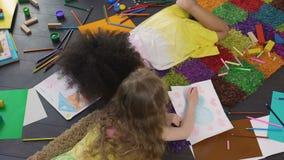 Krullende vrouwelijke jonge geitjes die op vloer liggen en met kleurenpotloden bij kleuterschool trekken stock videobeelden