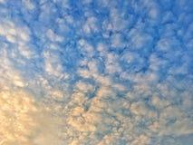 Krullende wolken op een blauwe hemel in de zonsondergang stock foto's