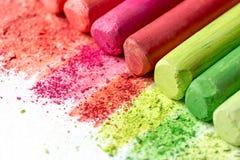 Krume und Klumpen der mehrfarbigen Kreide, Pastelle auf Weißbuch für Aquarell Gelb, rosa, rot, hochrot lizenzfreie stockfotografie