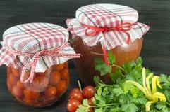 Krus av hemlagad ketchup och den körsbärsröda tomaten bredvid den nya körsbäret Royaltyfri Fotografi