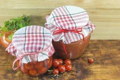 Krus av hemlagad ketchup och den körsbärsröda tomaten bredvid den nya körsbäret Royaltyfri Foto