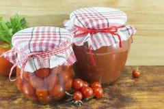 Krus av hemlagad ketchup och den körsbärsröda tomaten bredvid den nya körsbäret Arkivfoto