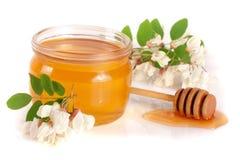 Krus av honung med blommor av akacian som isoleras på vit bakgrund Arkivbild