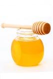 Krus av honung med den wood pinnen Fotografering för Bildbyråer