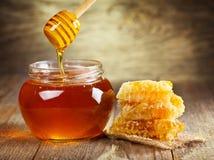 Krus av honung med honungskakan Arkivfoton