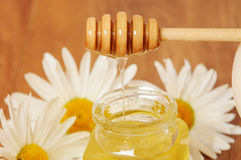 Krus av honung och en sked av honung Arkivfoton