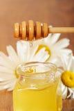 Krus av honung och en sked av honung Arkivfoto