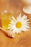 Krus av honung och en sked av honung Arkivbild