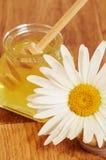 Krus av honung och en sked av honung Arkivbilder