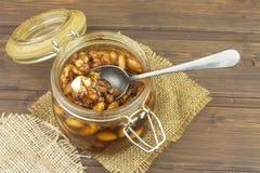 Krus av honung och muttrar Söt fest för snacking Inlagda valnötter i honung Royaltyfri Foto