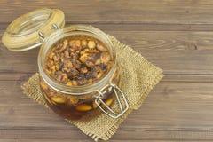 Krus av honung och muttrar Söt fest för snacking Inlagda valnötter i honung Arkivbild