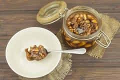 Krus av honung och muttrar Söt fest för snacking Inlagda valnötter i honung Arkivfoton