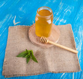 Krus av honung och skeden för honung Arkivfoto