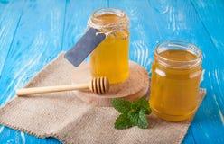Krus av honung och skeden för honung Arkivbild