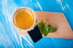 Krus av honung och skeden för honung Arkivfoton