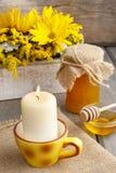 Krus av honung på trätabellen, bukett av solrosor i backgen Arkivbild