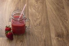 Krus av jordgubbefruktsaft Arkivfoton