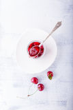 Krus av körsbärsrött driftstopp och några körsbär på tabellen Royaltyfria Foton