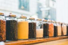 Krus av kaffebönor, ögonblickligt kaffe, socker och ingredienser i tappning tonar, djup av fälteffekt, med kopieringsutrymme Fotografering för Bildbyråer