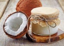 Krus av kokosnötolja och nya kokosnötter Arkivfoton