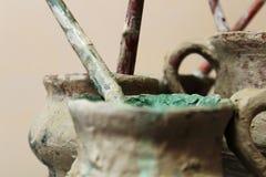 Krus av målarfärger och tofsar för keramiker arkivbilder