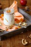 Krus av ny yoghurt med valnötter och aprikors arkivfoton