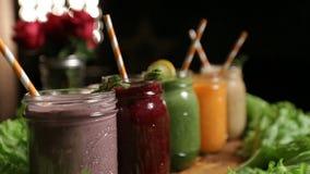 Krus av olika smoothies med sugrör för att banta