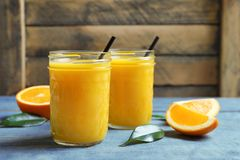 Krus av orange fruktsaft och nya frukter Royaltyfri Foto
