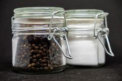 Krus av saltar och pepprar p? svart bakgrund fotografering för bildbyråer