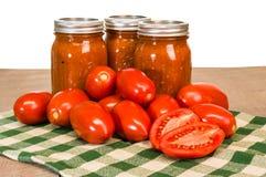 Krus av tomatsås med degtomater Royaltyfria Bilder