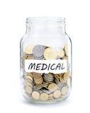 Krus med mynt på läkarundersökning Arkivfoton